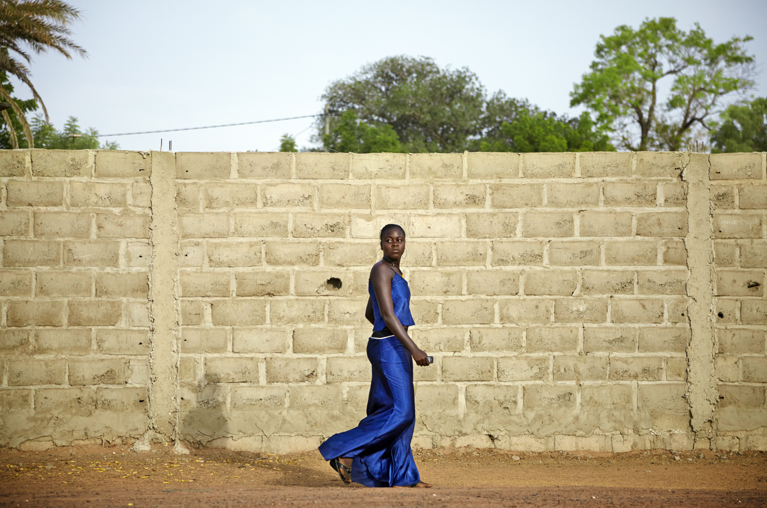 Blue Dress , Senegal 2011  Archival Pigment Print 22 x 33, Edition of 7 (1-3 available) $2200  The road was endless and there was no time to stop. Hour after hour, photogenic moments passed before my eyes and a knot grew in my stomach over not being able to capture what unfolded before me. I then decided to start shooting through the moving car window when this woman in blue appeared.