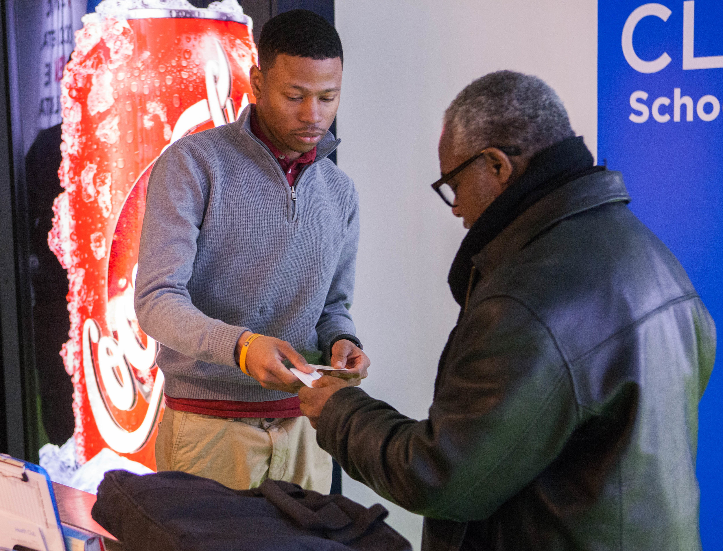 Robert hands a business card to an elderly man at a coffee shop.