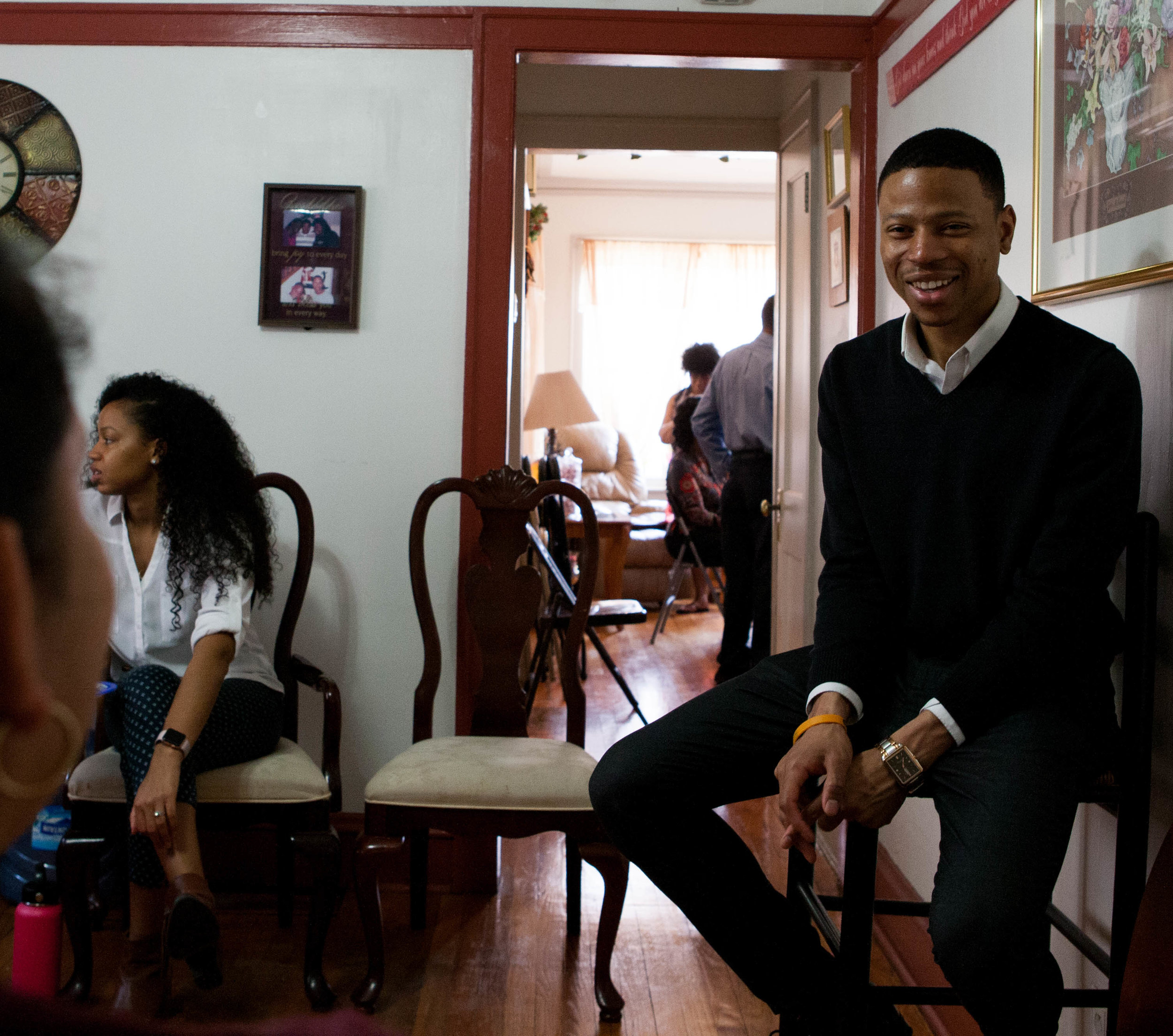 Robert sits and smiles to the camera at a fundraiser at his mother's home.