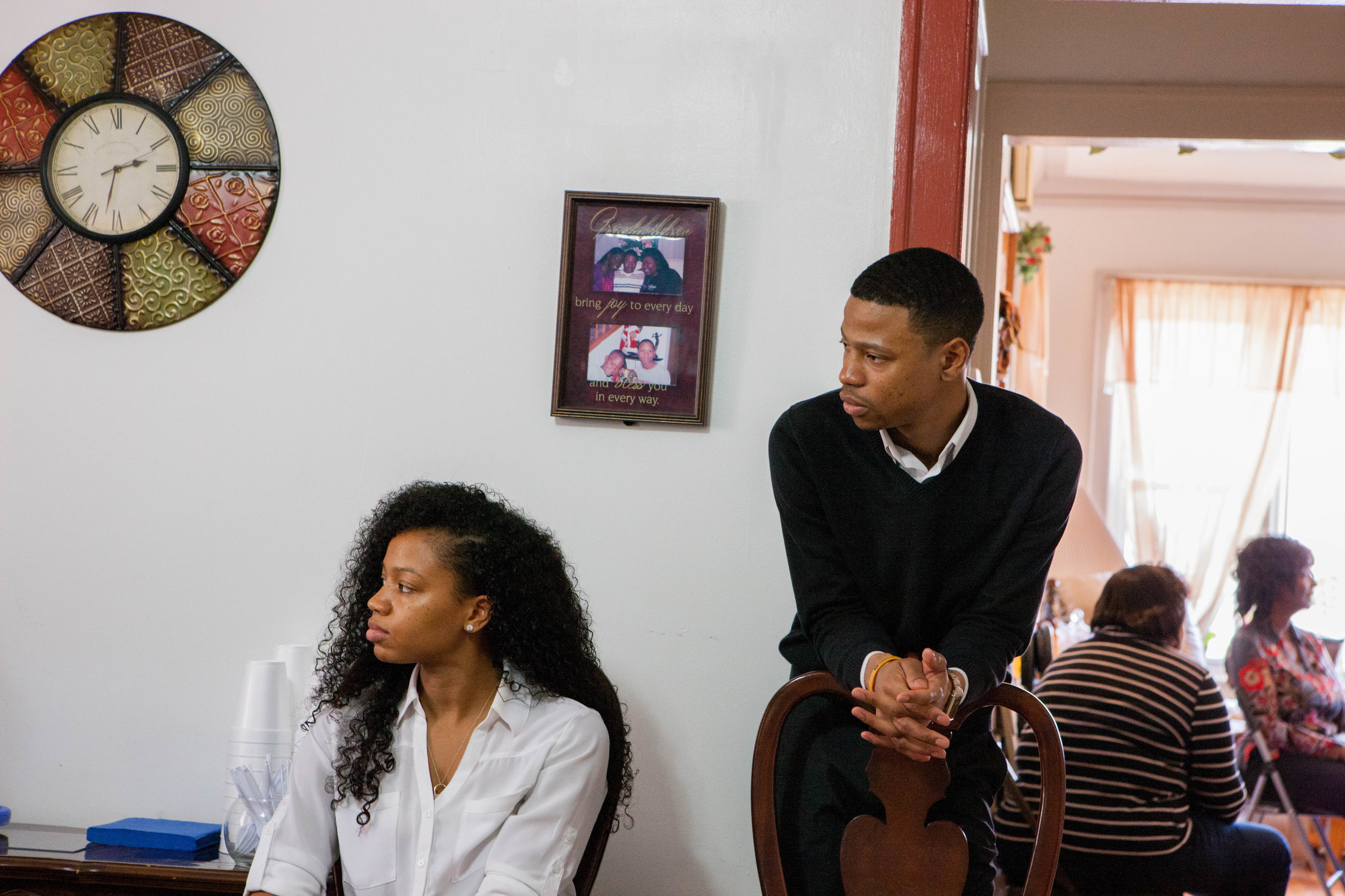 Robert and Brittani listen to an individual off camera at a fundraiser at Robert's mother's home.