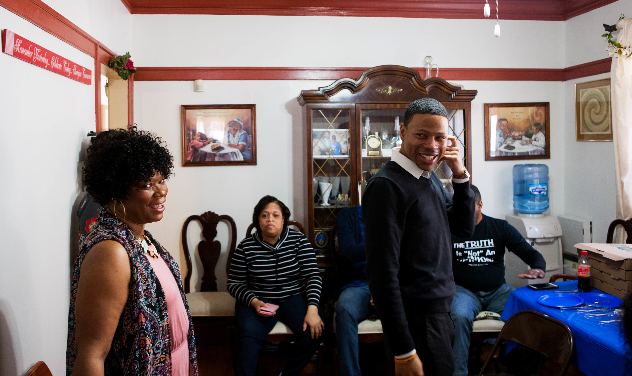 Robert and his mother stand in the center of the room while Robert addresses guests at a fundraiser at her home.