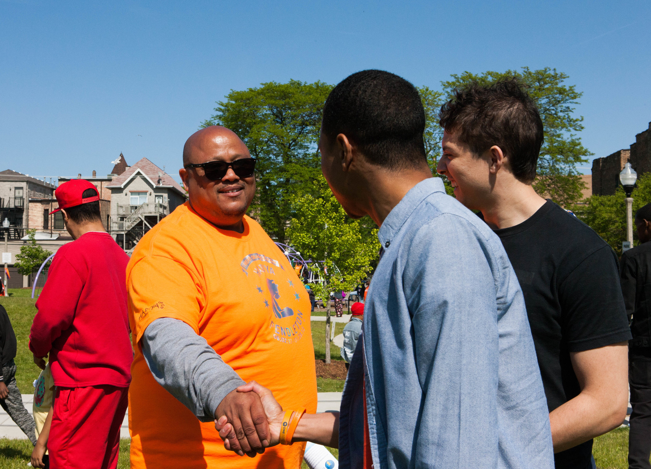 Robert shakes a man's hand at the Wear Orange Peace Party.