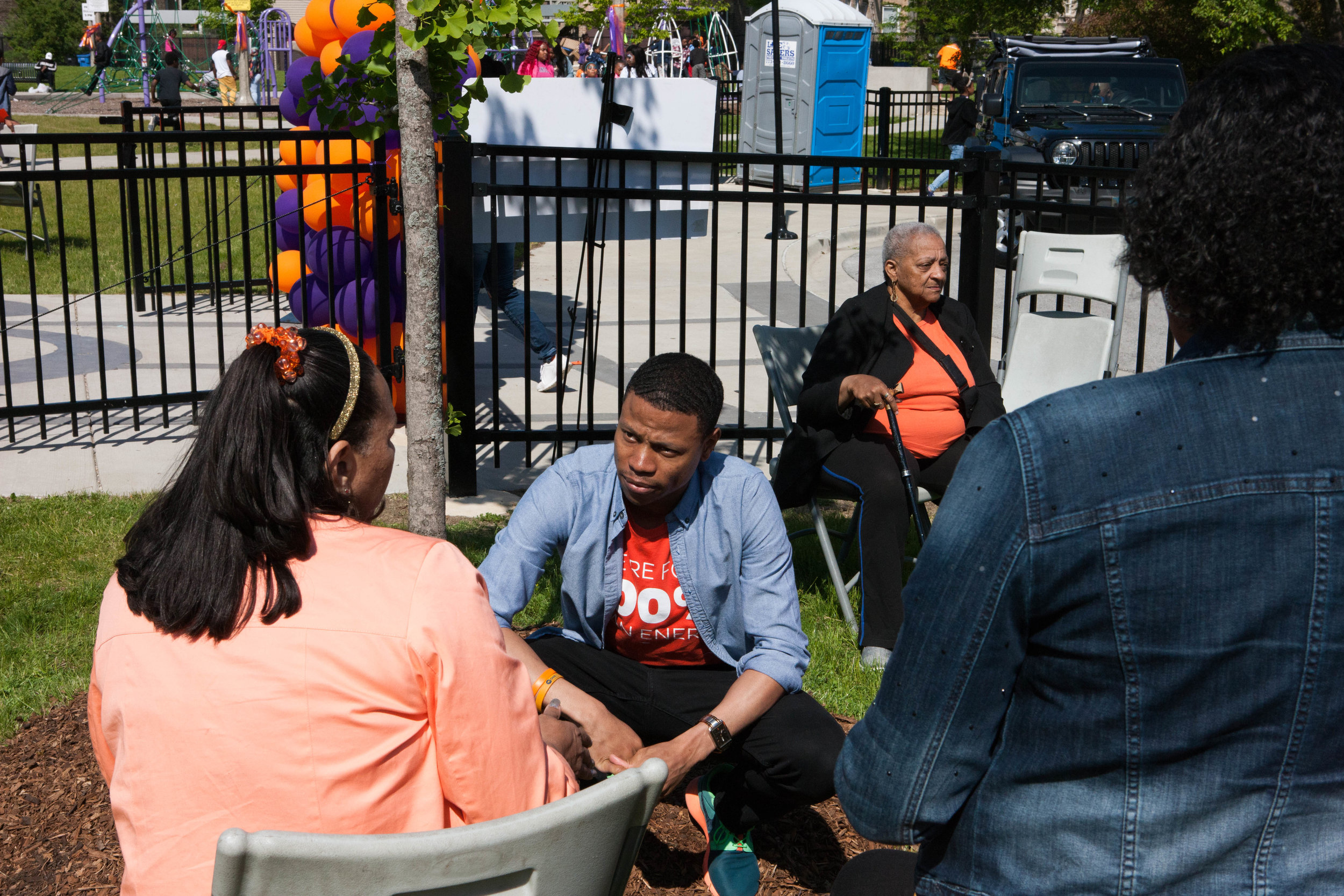 Robert crouches and listens to a woman's concerns at the Wear Orange Peace Party.