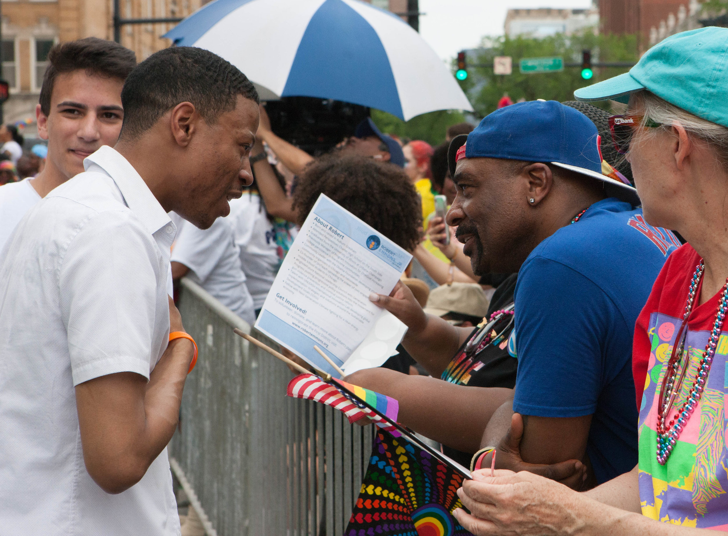 Robert speaks with a man across a barrier at the Pride Parade.