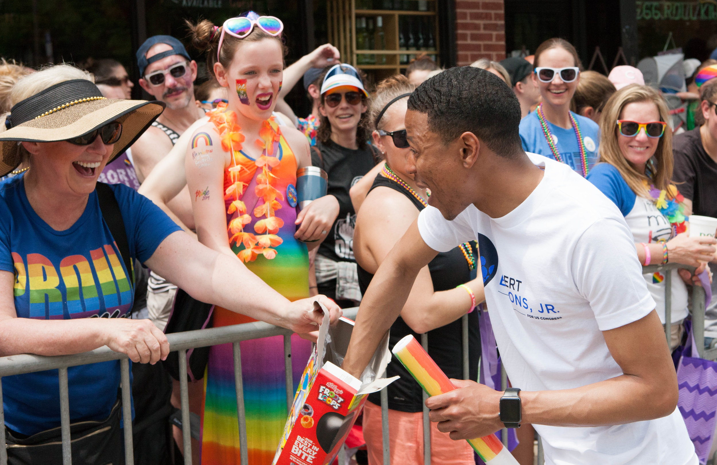 Robert laughs with a woman as he reaches into a box of cereal she holds at the Pride Parade.