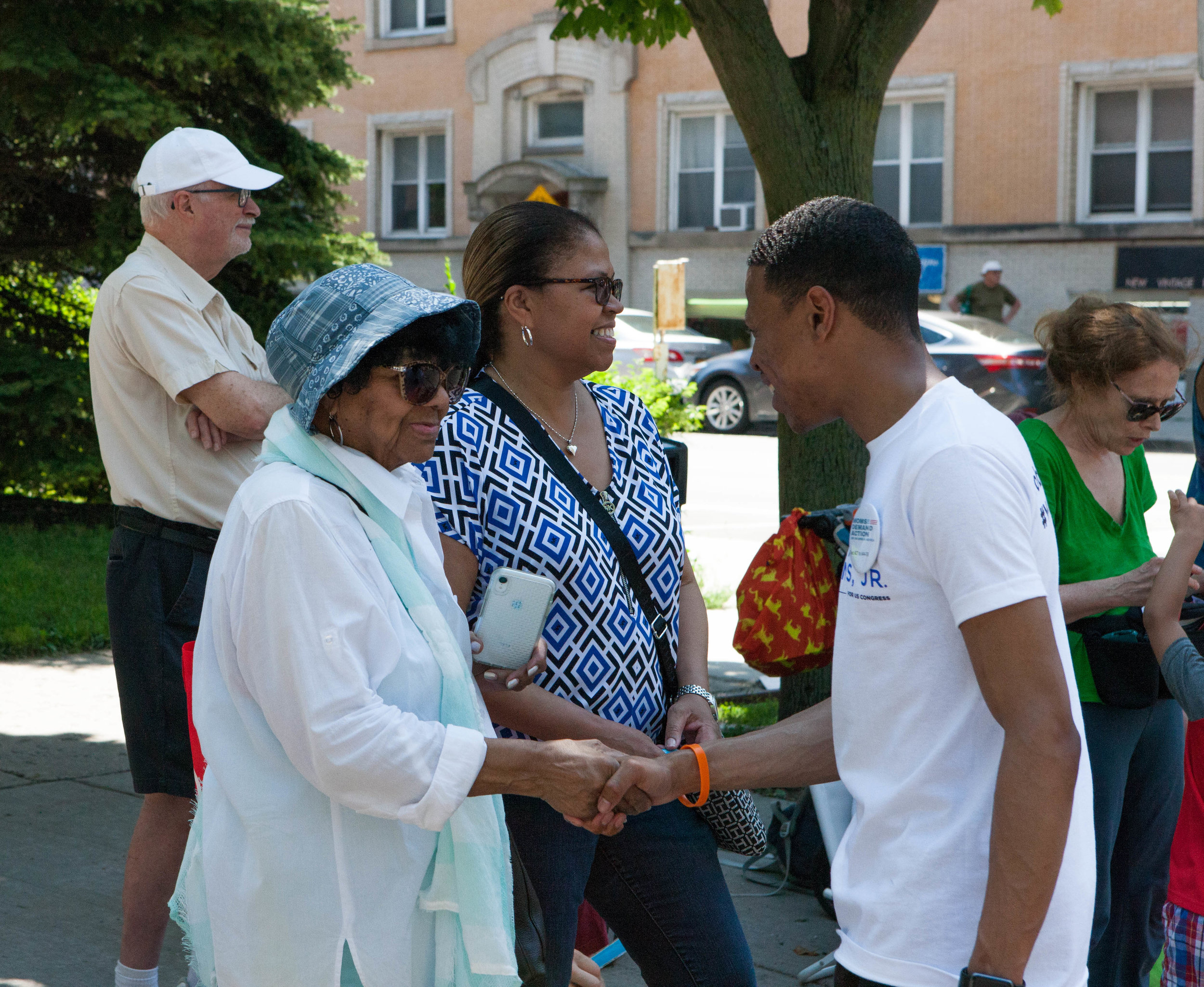 Robert shakes the hand of an elderly woman at the 4th on 53rd Parade.