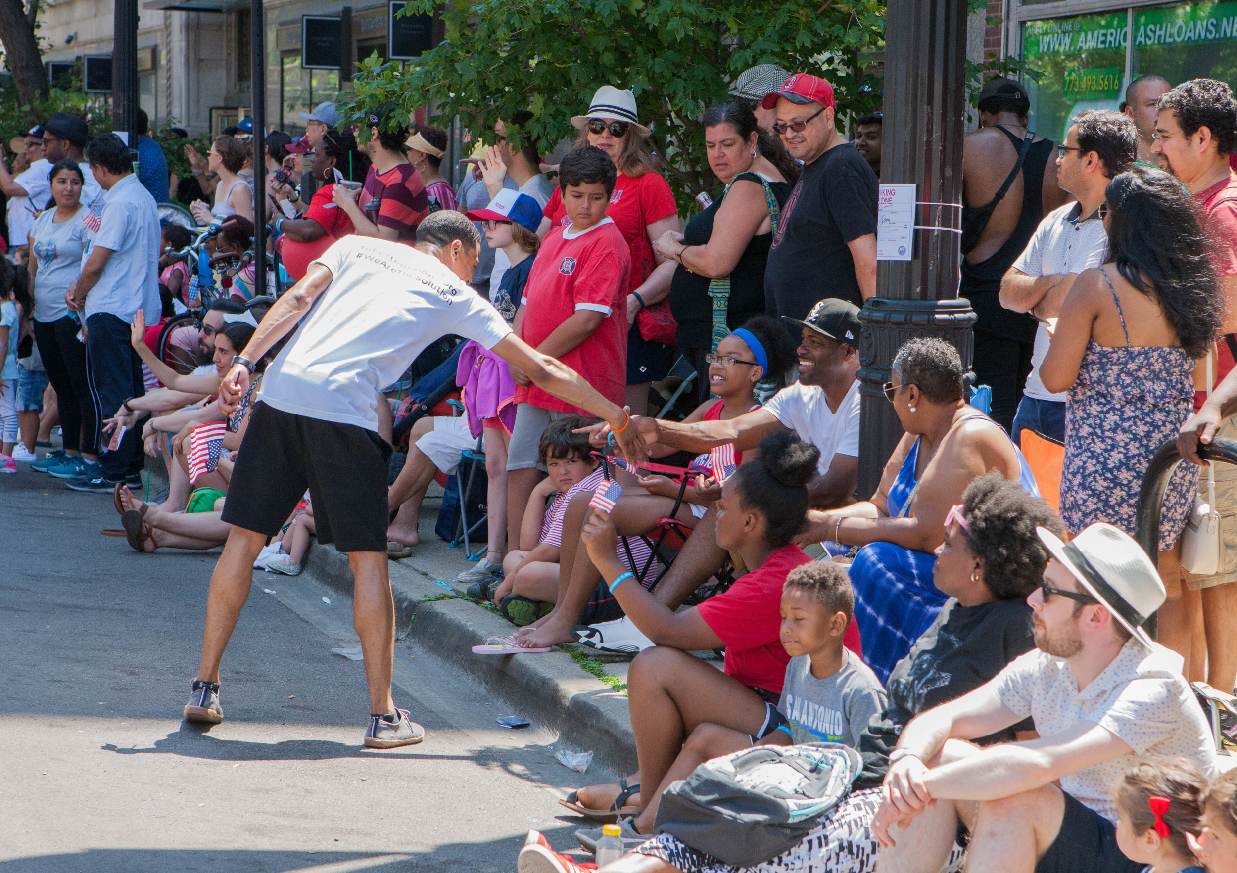 Robert reaches into a crowd on onlookers to shake a man's hand at the 4th on 53rd Parade.