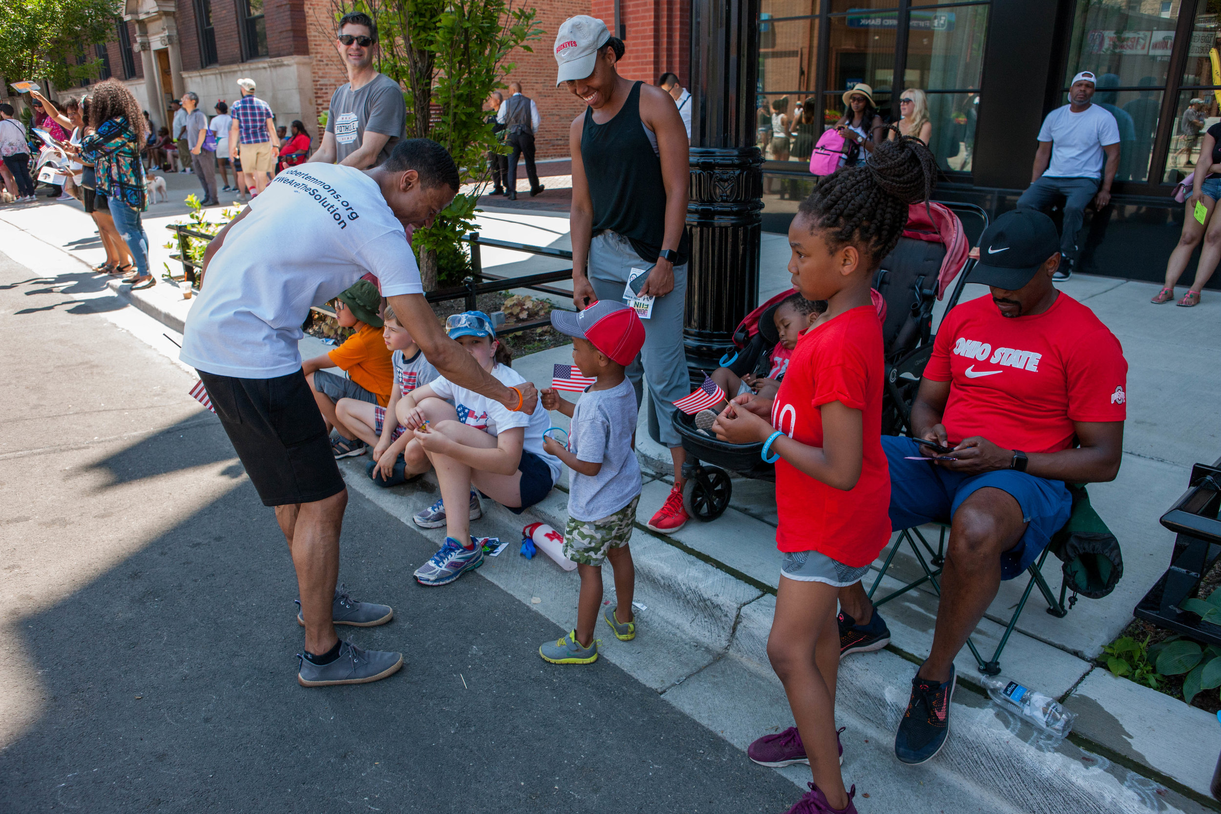 Robert reaches down to shake the hand of a child at the 4th on 53rd Parade.