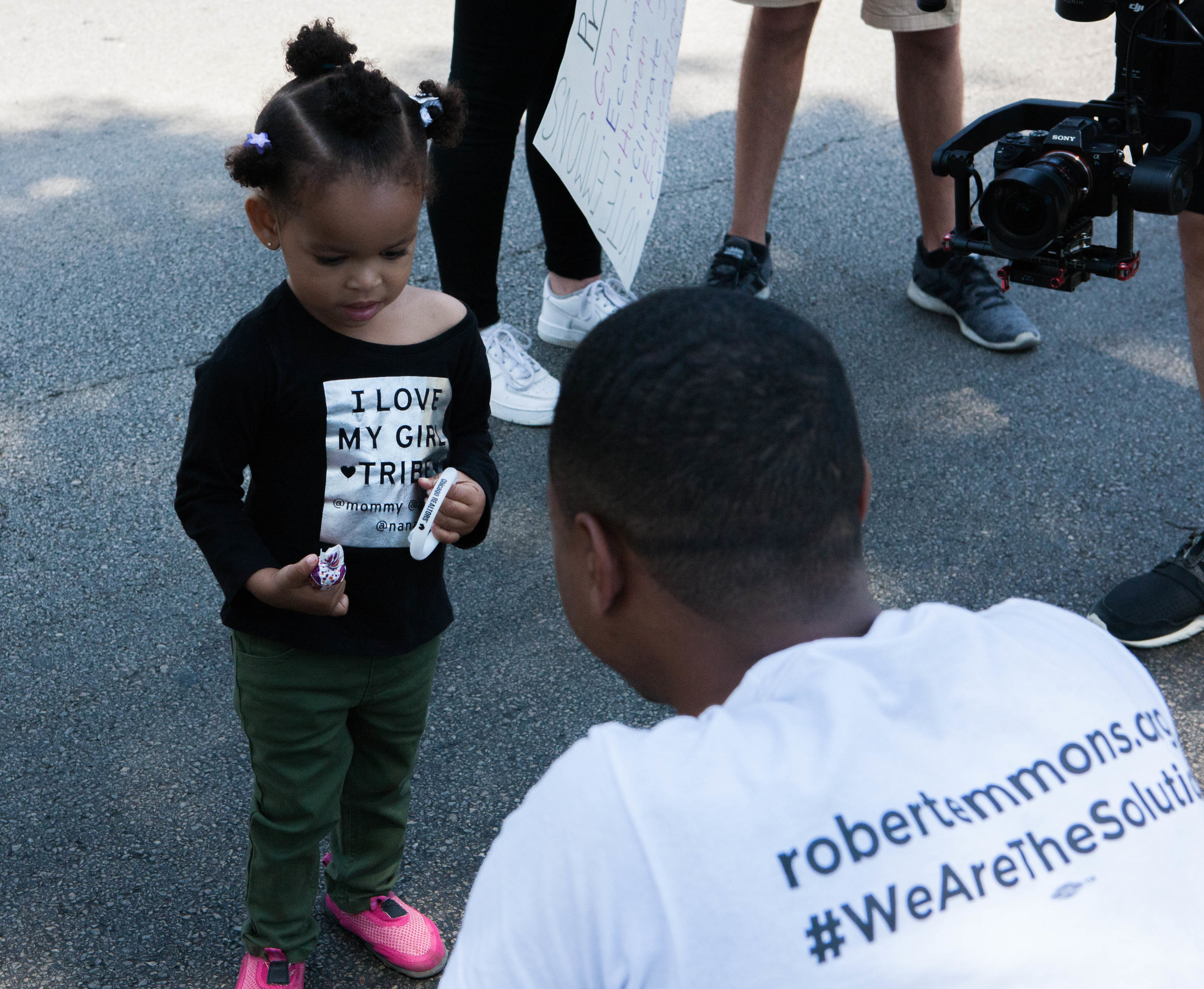 Robert Emmons Jr. crouches to speak with a young girl at the Bud Billiken Parade.
