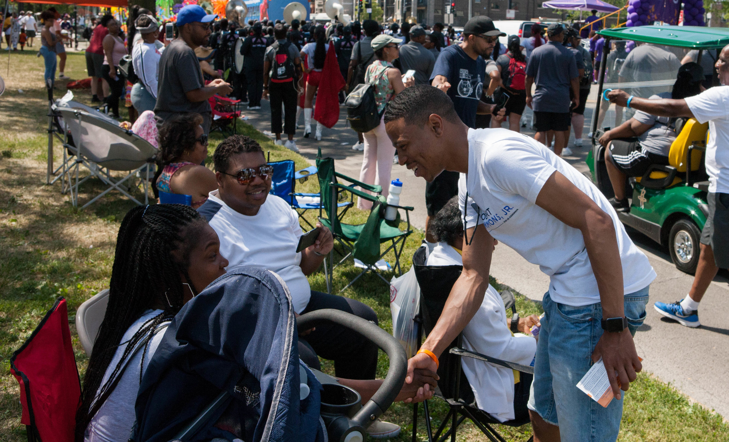 Robert shakes the hand of a supporter from at the edge of the Bud Billiken Parade.