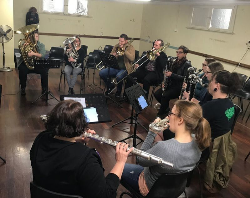 Aviva Endean leads the wind and brass sectional, with Deborah May stealthily filming in the background