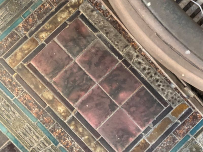 The tiling at the base of one fireplace in the main space.