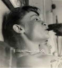 A photo of Eliane Radigue smoking a cigar, taken by her husband at that time, French artist Arman.