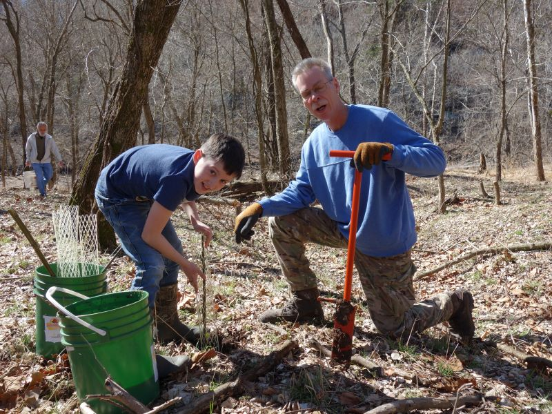 SCC members plant bare root trees and install plastic protectors.