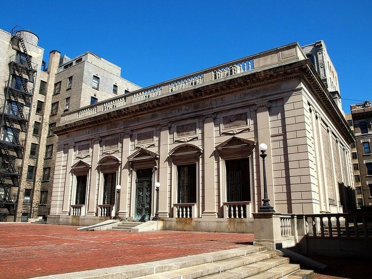 In 1923, the American Academy moved to its current location on Audubon Terrace in Washington Heights. Its beaux-arts administration building, pictured here, was designed by Academy member William Mitchell Kendall, from the architecture firm McKim, Mead, & White, and houses the library, archives, members' meeting room, exhibition galleries, and staff offices. A second, adjoining building, designed by Academy member Cass Gilbert, was completed in 1930. In 2005, the Academy purchased the former headquarters of the American Numismatic Society, its neighboring building on Audubon Terrace. A glass link now connects the Academy's existing galleries to newly renovated ones in the former Numismatic building.