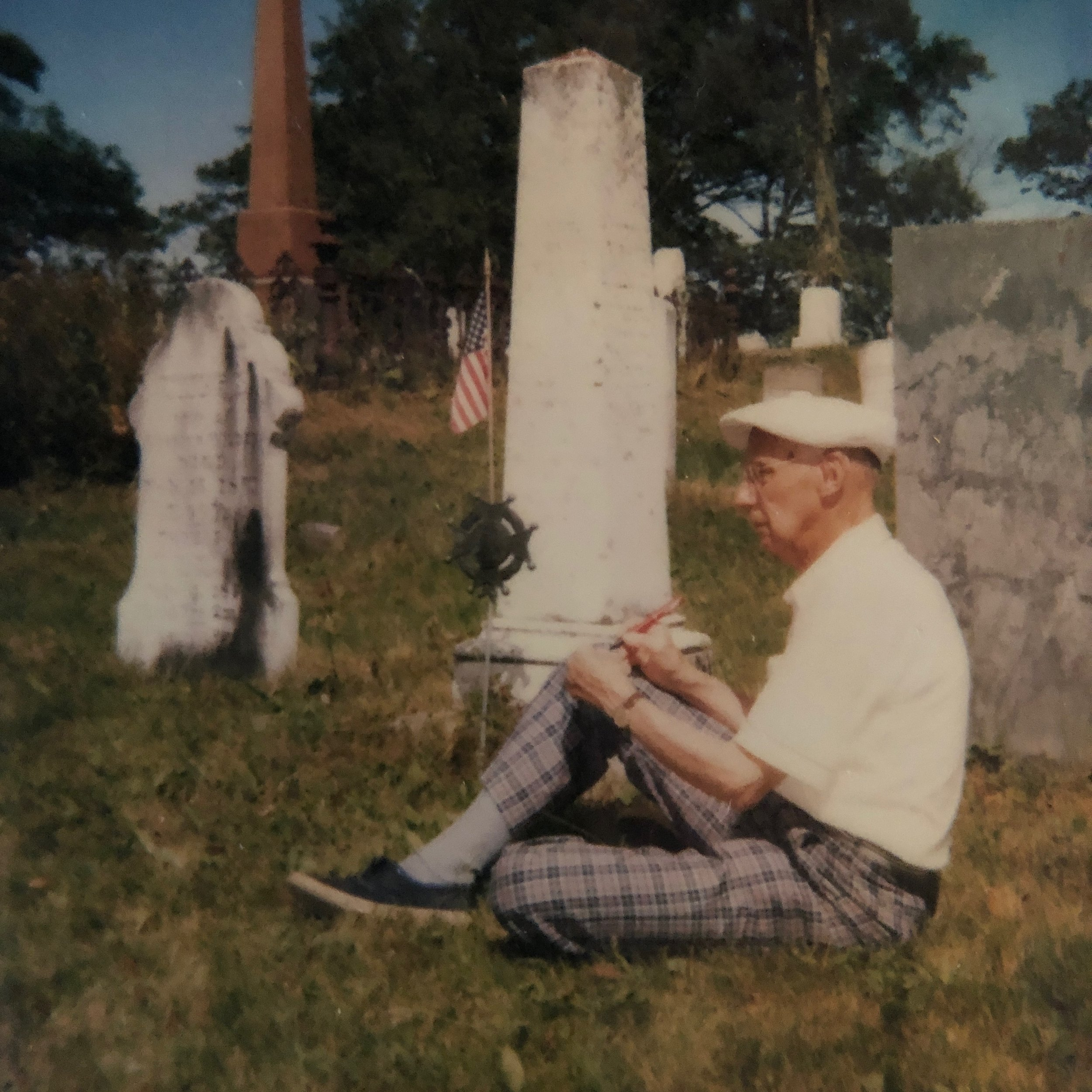 Amos Niven Wilder sketching beside Captain Wilder's gravestone.