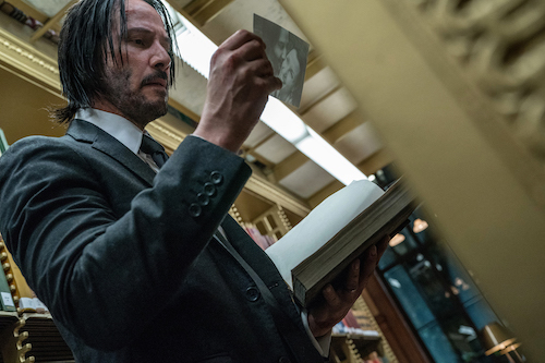 John Wick picking up items hidden in an archival library.