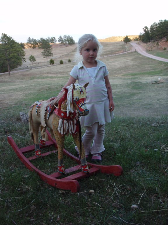 A model horse, complete with porcupine-quilled pad saddle, martingale, crupper and leg cuffs.