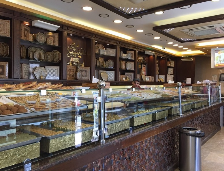 A popular Syrian pastry store in Amman, beautifully displaying Arabic sweets.