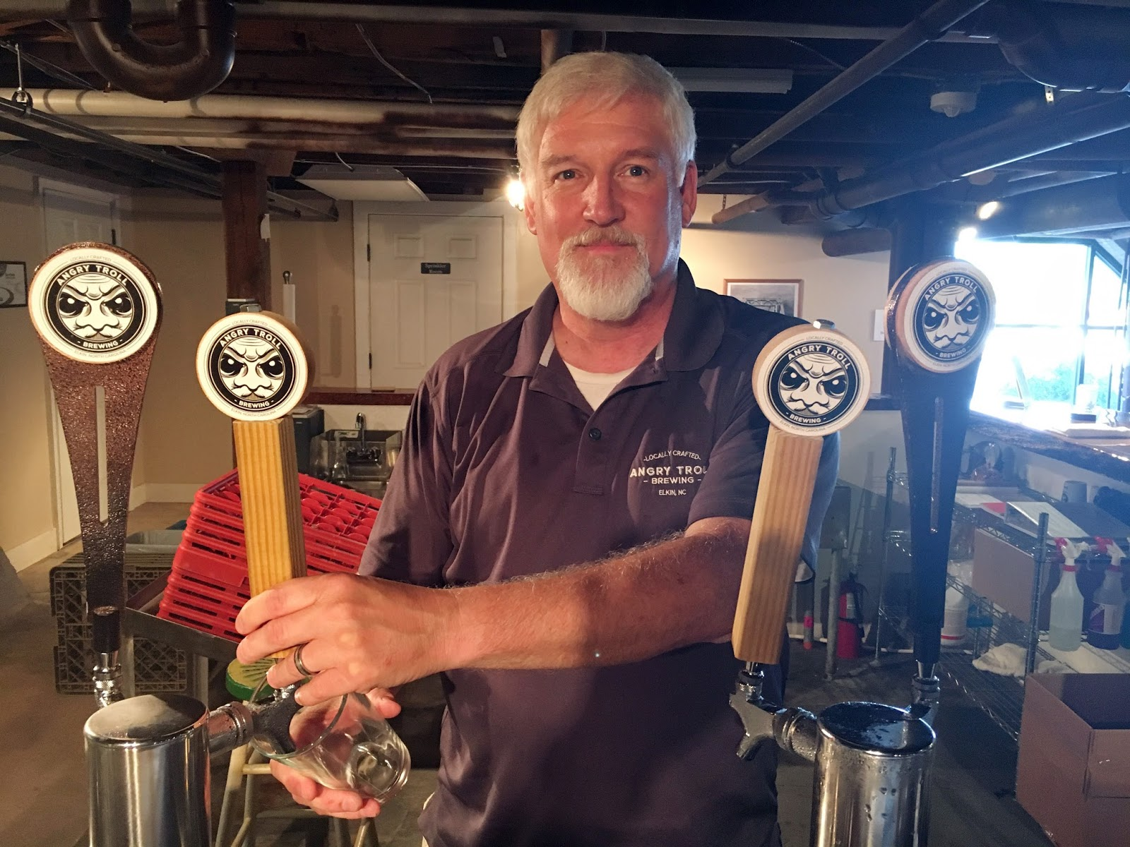 Angry Troll co-owner Bob Puckett pours a pint.