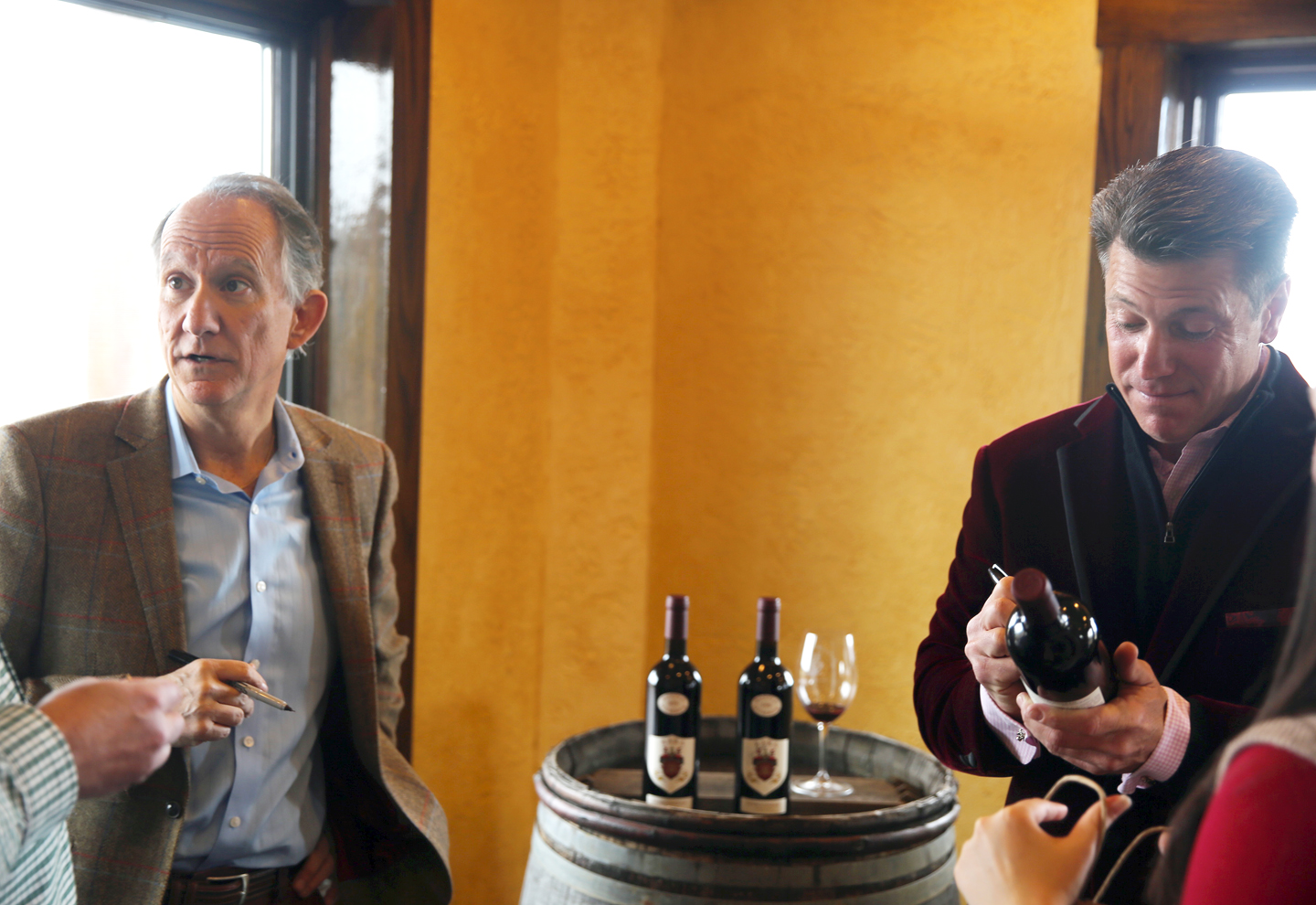 Jay Raffaldini (left) and JW Ray (right) sign bottles of their collaboration wine, Sisboombah.
