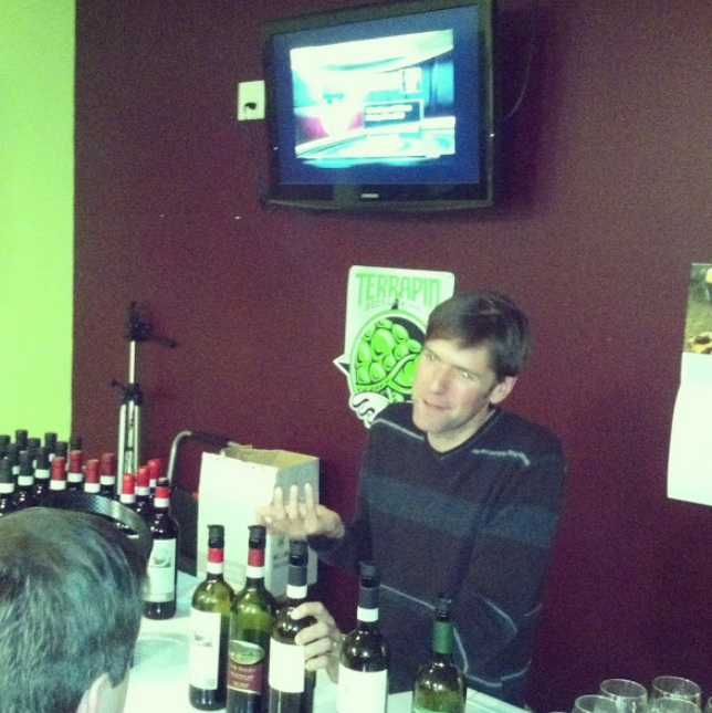 Jay Murrie pours several Italian wines for the patrons at Wine 101