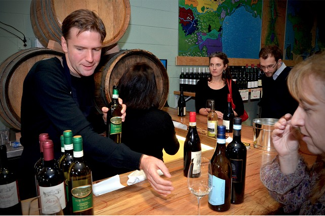 Jay Murrie with Piedmont Wine Imports pours wine for customers at Wine Authorities