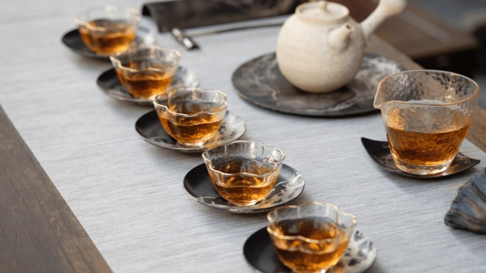 vijf kopjes thee op tafel met een theepot en een glazen kan