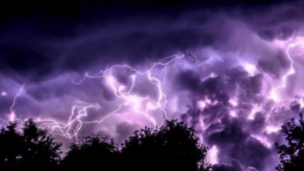 bliksemschichten in een paars/blauwe lucht met bomen op de voorgrond