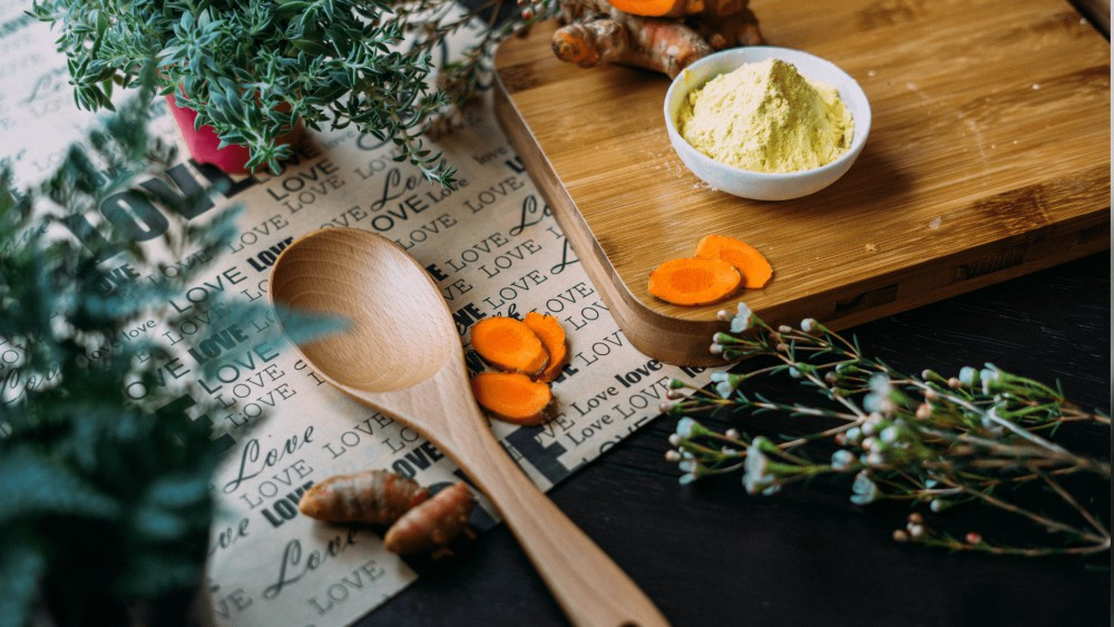 Kurkumaschijfjes op een houten plank met een kommetje kurkumapoeder. Kurkumaschijfjes op een 'love' placemat met daarnaast een houten lepel en kruiden en kurkumawortel.