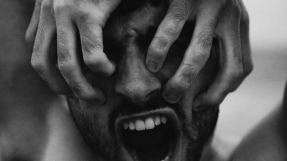 een wanhopige man met zijn handen voor zijn ogen met zijn mond wijdopen
