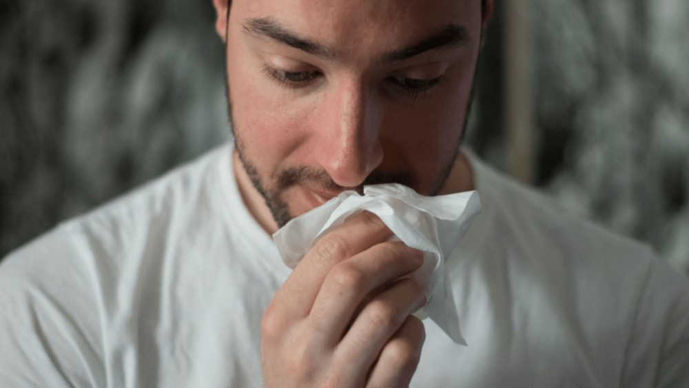 een snotterende man met een zakdoek in zijn hand
