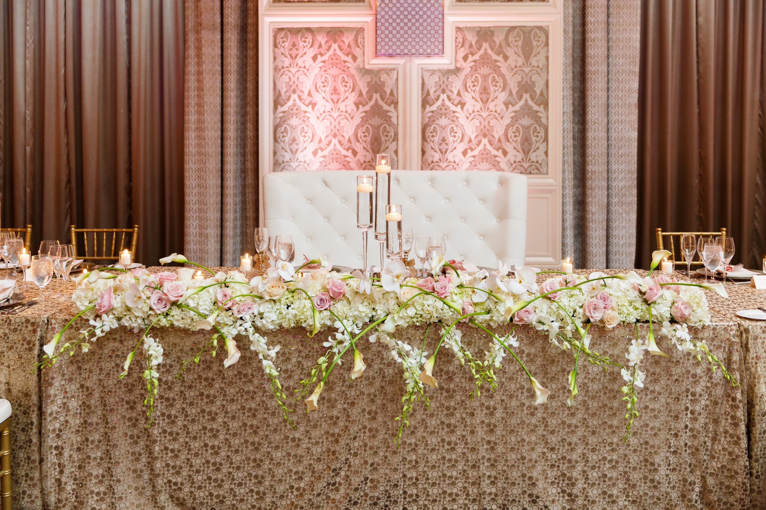Overflowing flower runner on head table with sequin linen at Four Seasons Orlando