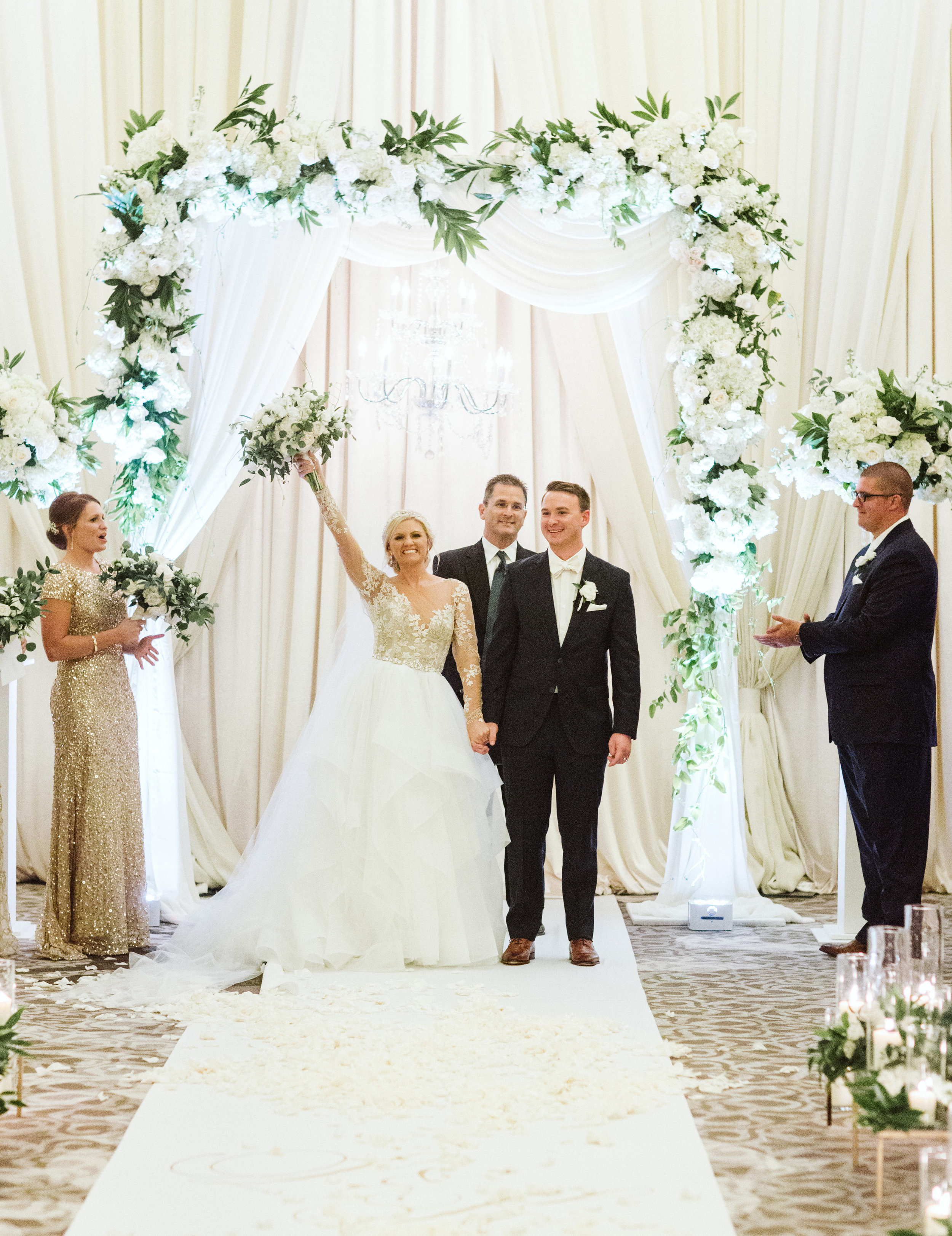 White and greenery ceremony structure with chandelier and hayley paige gown