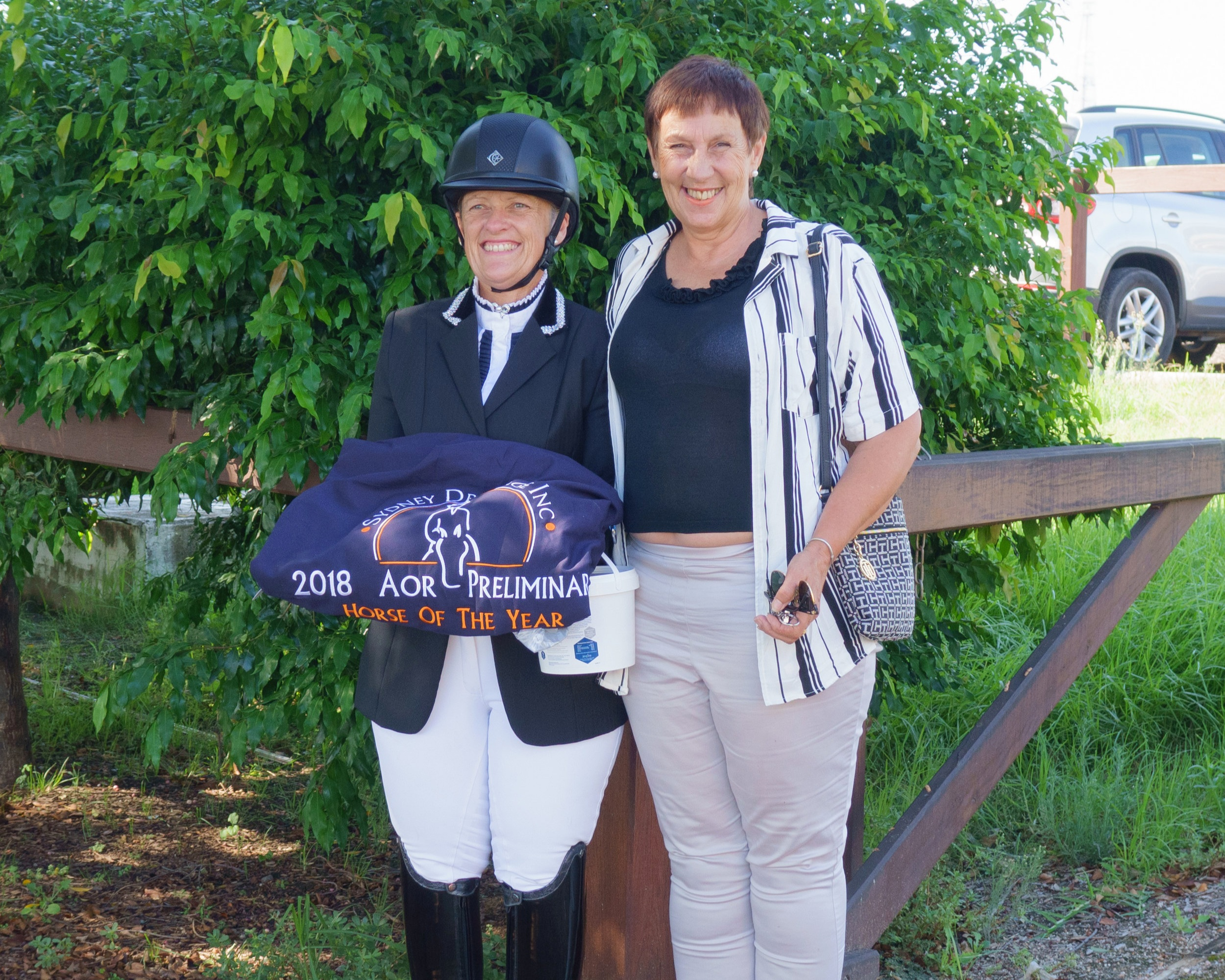Jennifer wales holding the zilco trophy rug and equestrian news aor prize, photographed with zilco representative kelly king
