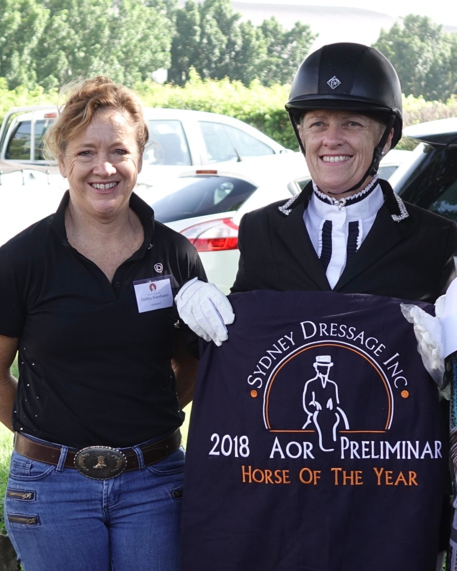 Jennifer wales being presented the award for 2018 amateur owner rider preliminary horse of the year award by president debbie eisenhauer-rodney.