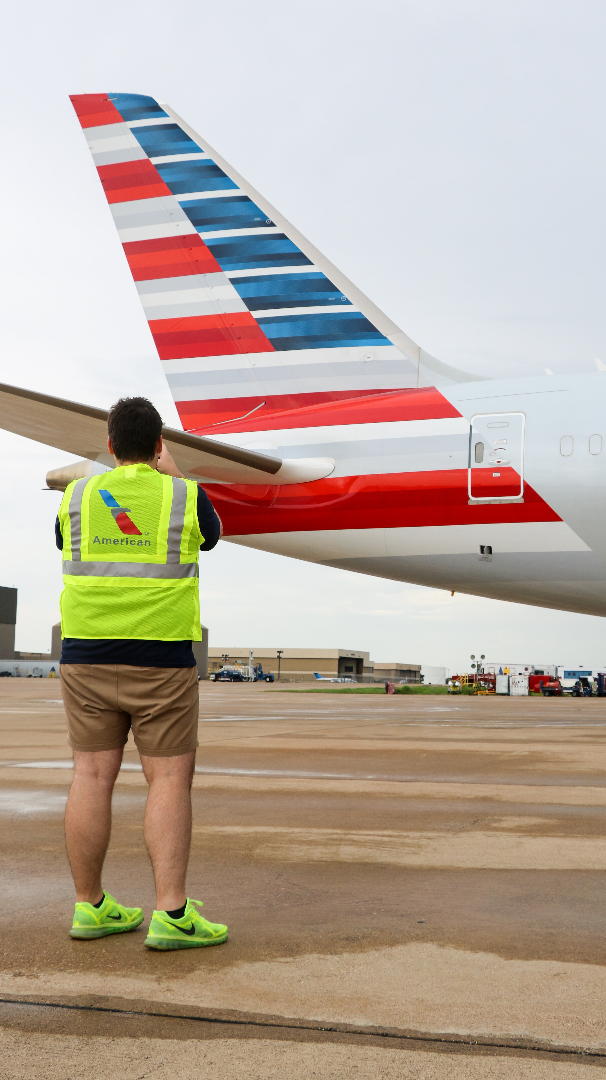 Decked out in a neon high-visibility vest, one of the attendees of the rainy tour snaps a picture of the tail of an American Airlines Boeing 787-9 Dreamliner.
