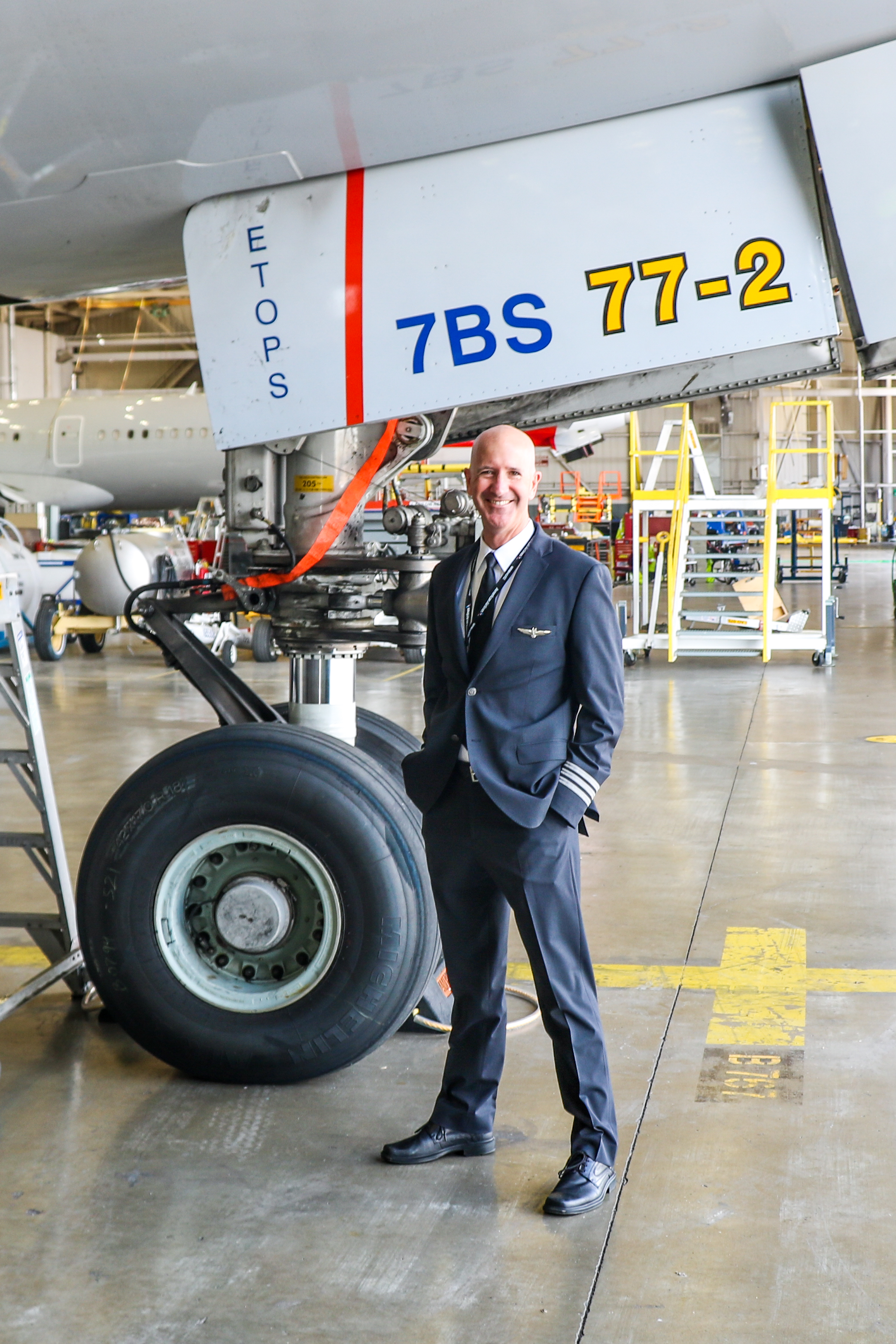 American Airlines Boeing 777 First Officer Brad Kelly stands in front of the landing gear of an American 777-200 in DFW's west hangars. Kelly had flown that particular airframe, fleet number 7BS, multiple times during his multi-year tenure at American.