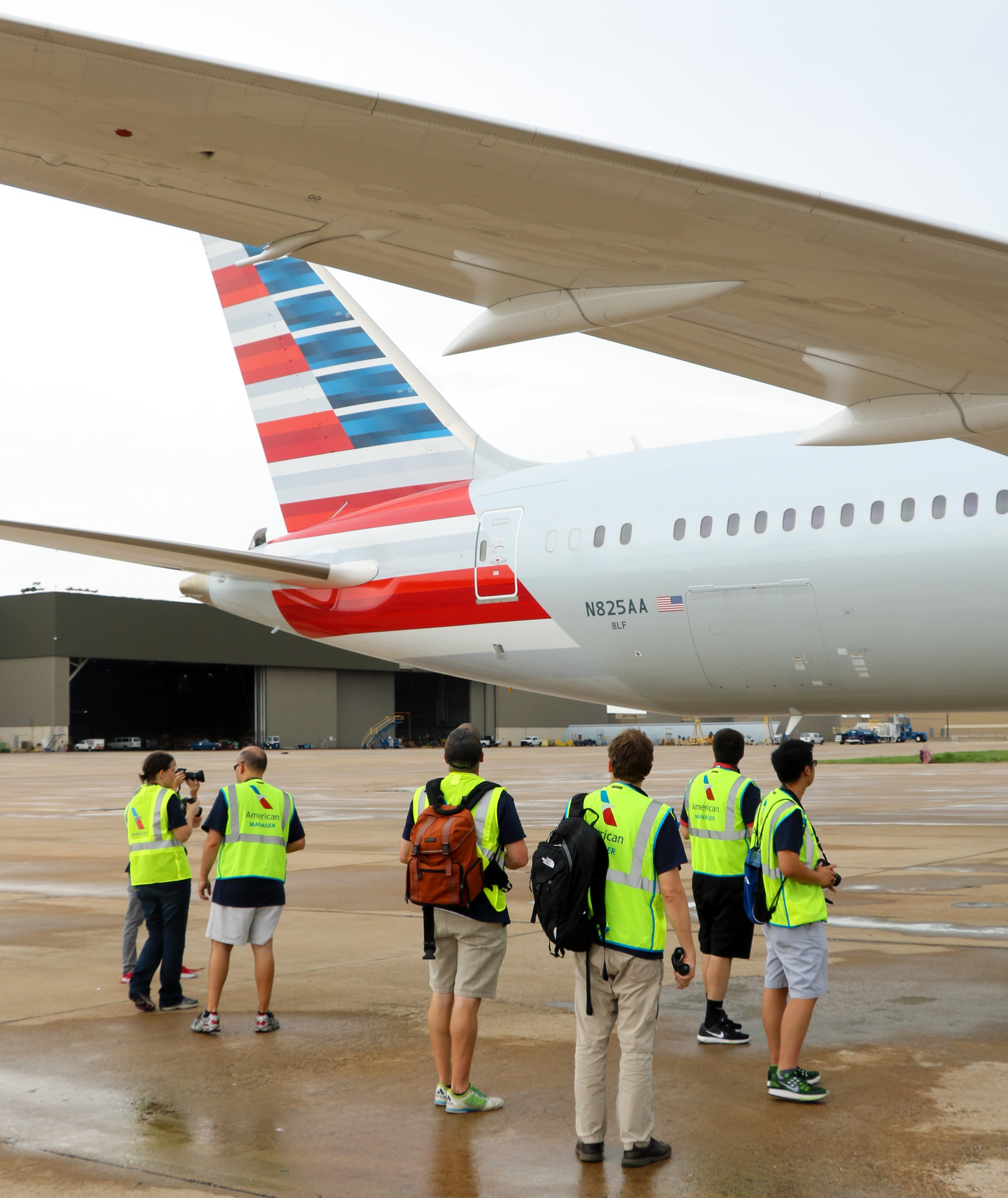 Standing under the wing, the participants in DFW's AAviationDay collectively admire an American Airlines Boeing 787-9.