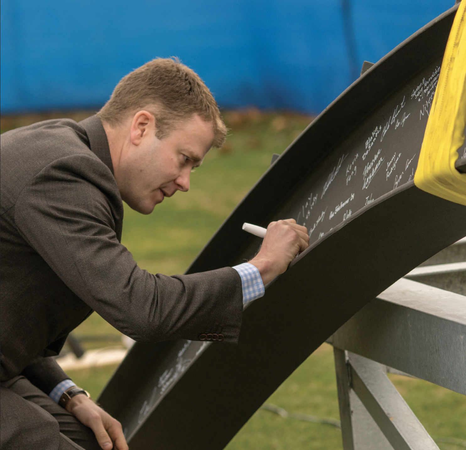 Joining the 90 members of the Class of 2018, Chris Winn '99 affixes the final signature to the last steel beam to be added to the Winn Science Center during the topping off ceremony in January 2018.