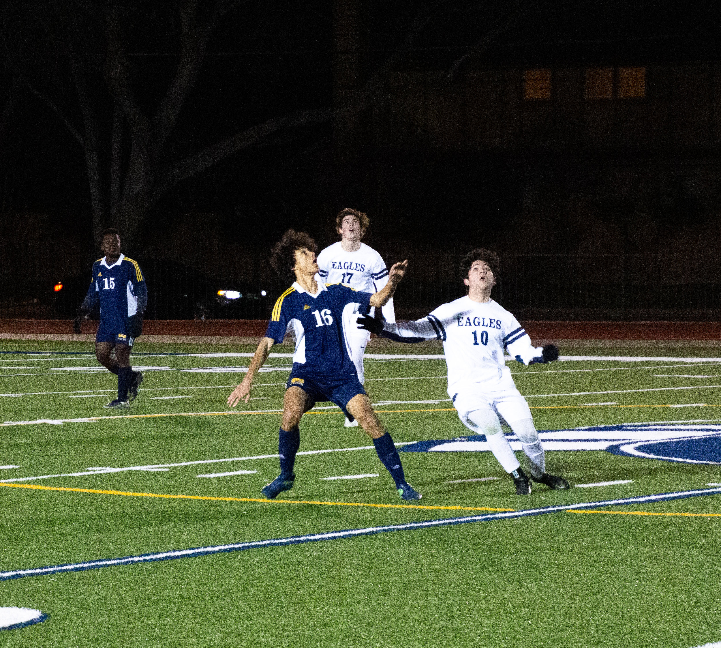 Junior midfielder Miles Hartley fights off and ESD defender as he prepares to head the ball back across the 50-yard line.