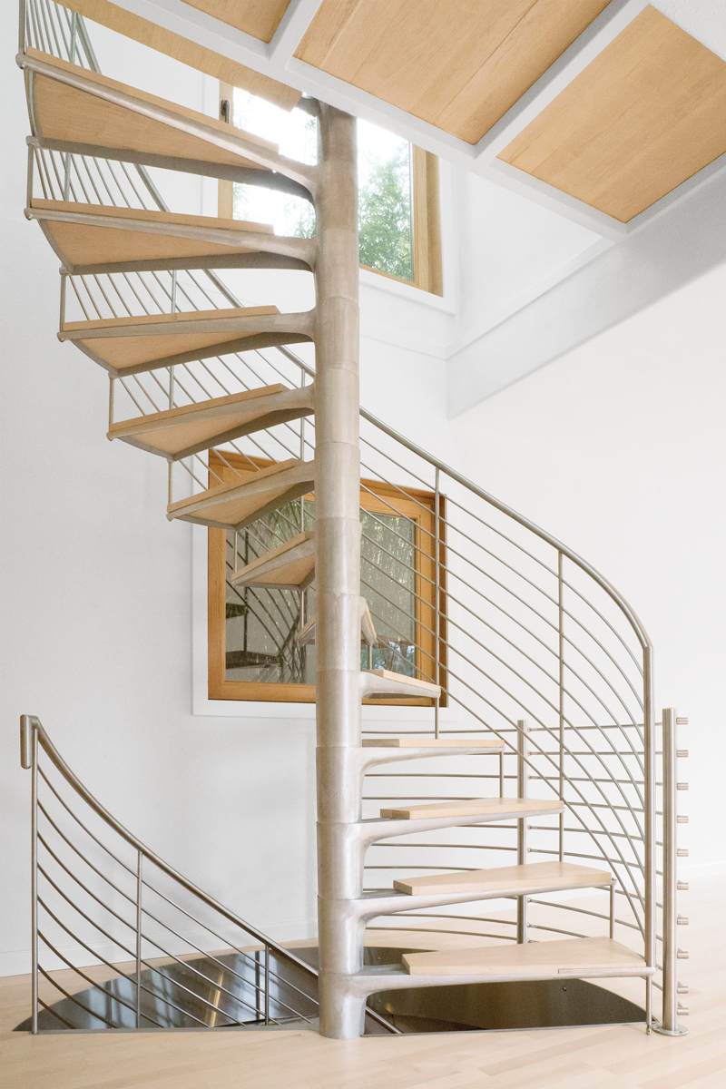 Mount Tamalpais Spiral - Helical brushed stainless steel cap rail and horizontal pickets for three-story spiral staircase remodel. Custom handrail terminations and stainless steel glass railing framing and hardware. Private residence, Mill Valley, Marin