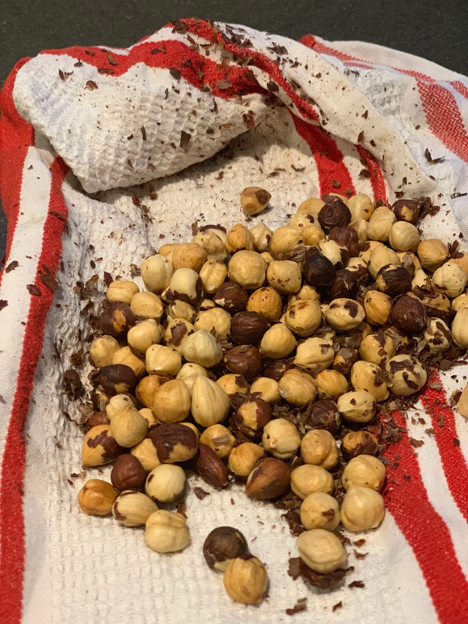 Rubbing the hazelnuts ina towel right after they're baked helps the skin fall off