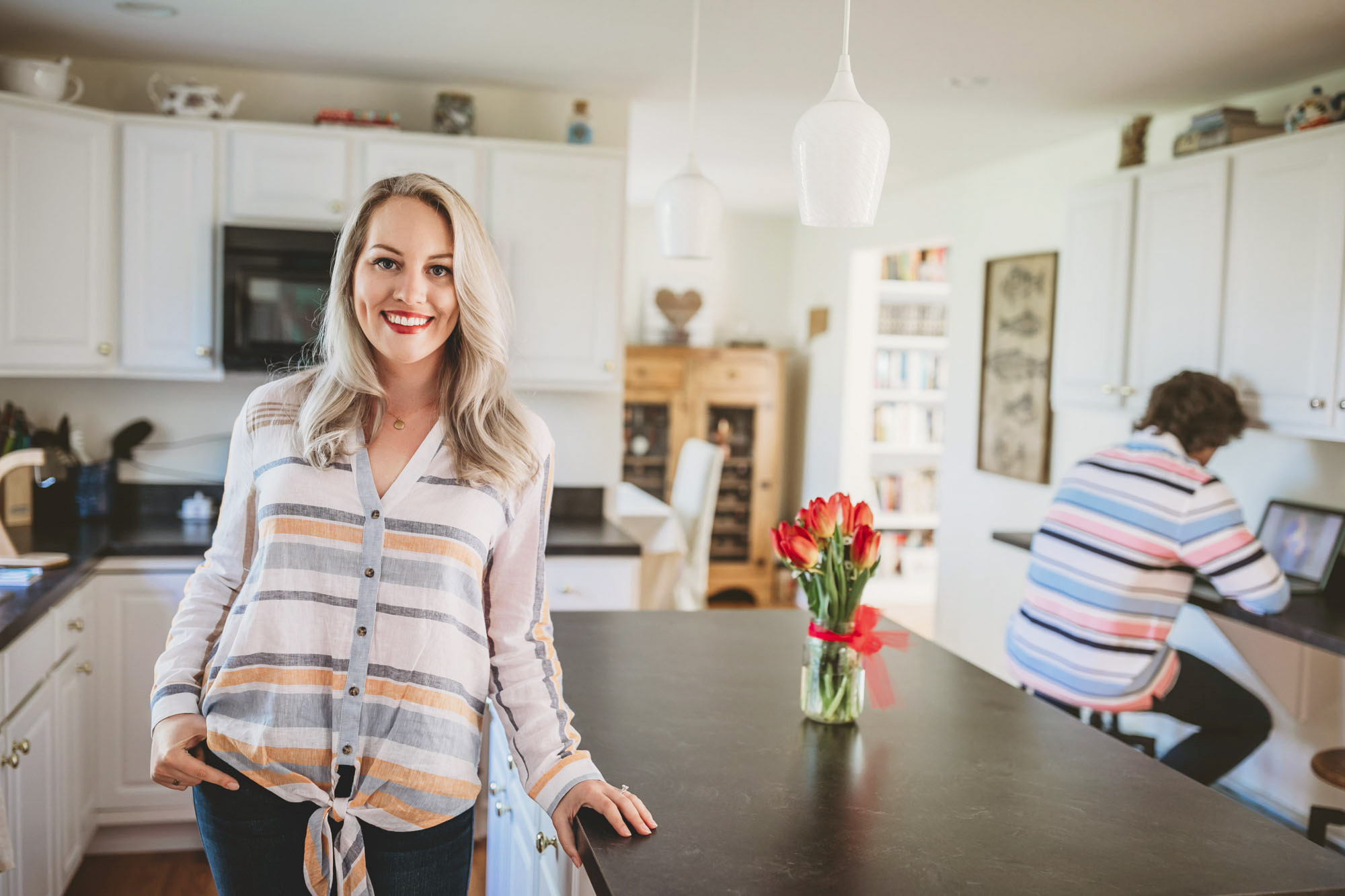 Rebecca Atkins poses in her New London home while her foster son looks over schoolwork on his computer in the background.