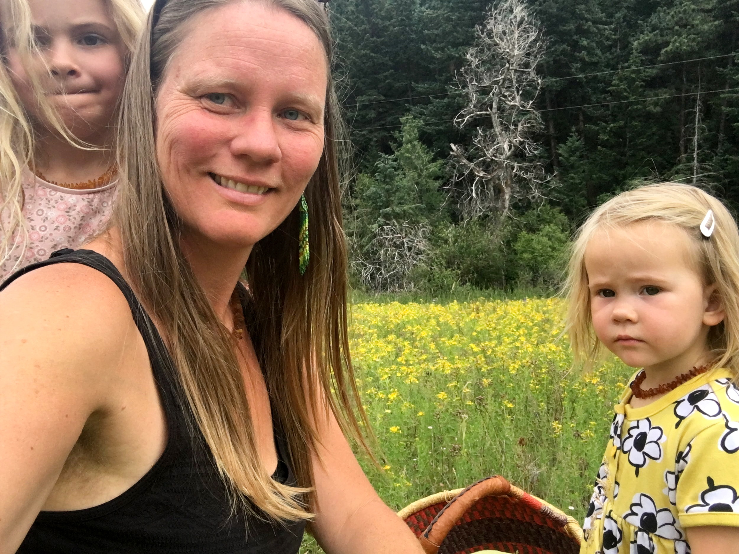 -Astrid with her two daughters in a field of flowering St. Johnswort-