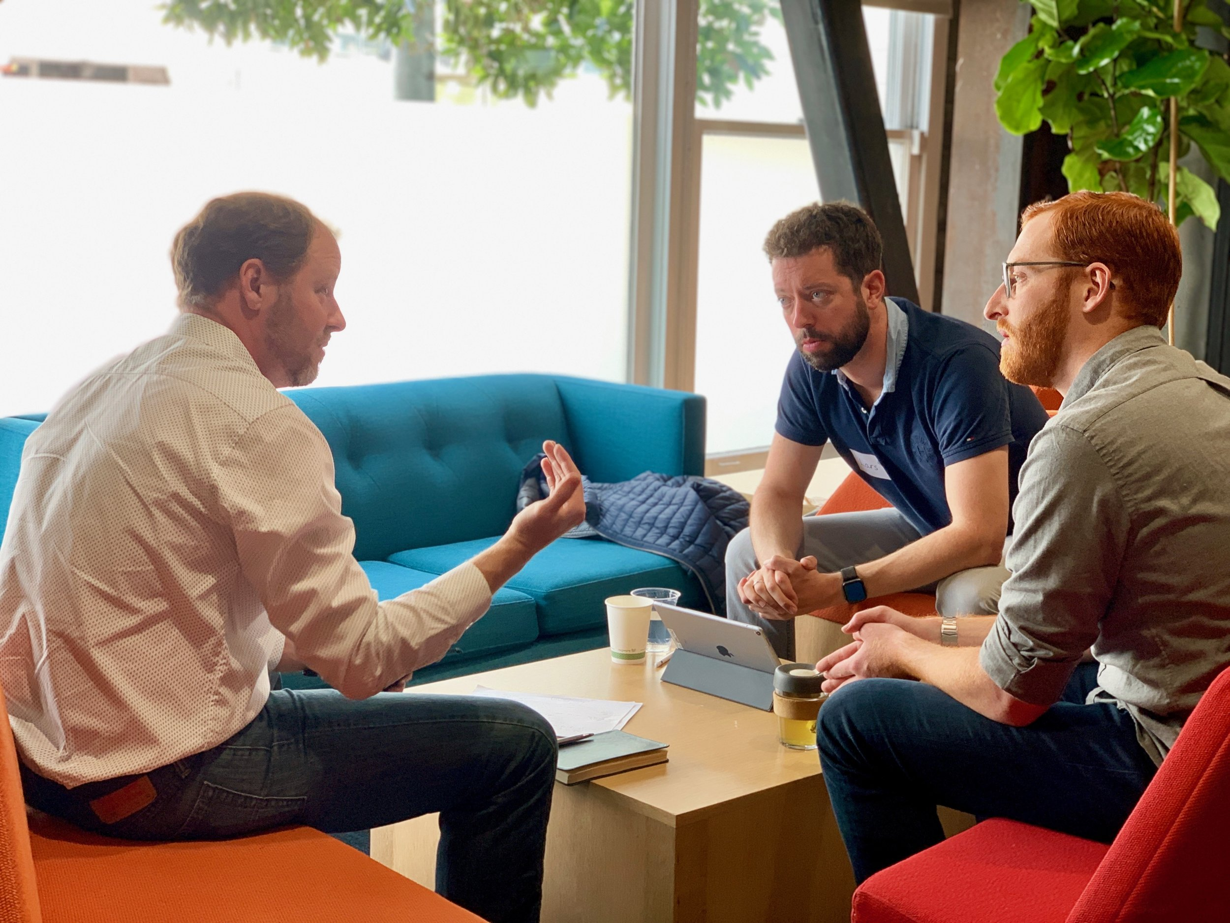 MAN Impact Accelerator social entrepreneur  Noah Perin  from  VIA Global Health  sitting with his lead mentor  Dr. Lars Eiermann  from MAN Truck & Bus and his tech mentor   Stephen Morseman   from Uber.