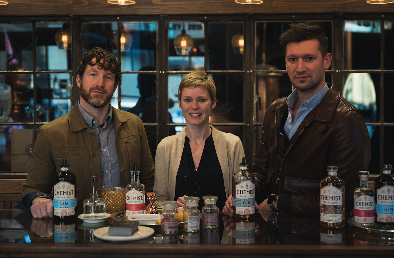 SPIRITED DEBATE: Apothecary Beverage Co. owners, from left, Brandon Horne, Danielle Donaldson and James Donaldson recently opened The Chemist distillery and Antidote bar on the South Slope. State and federal legislative changes have helped open up opportunities for craft distillers in recent years, but many distillers say North Carolina still has a long way to go. Photo by Luke Van Hine