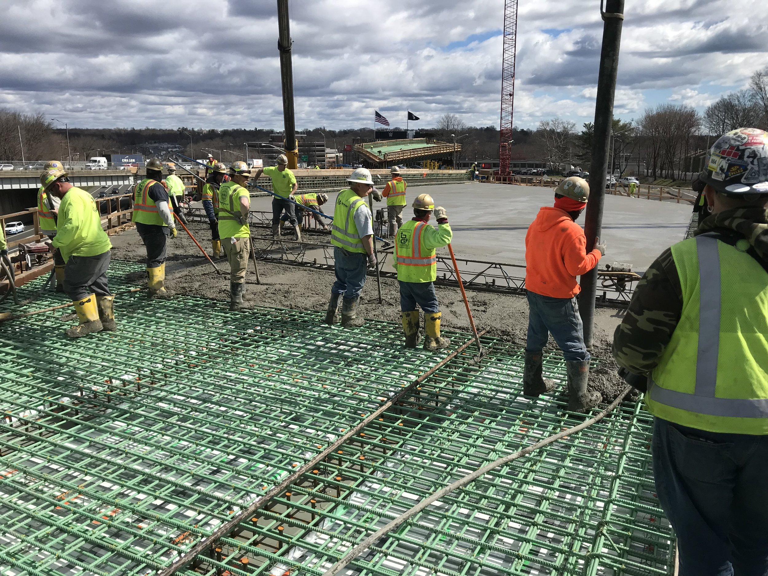Workers guide concrete over rebar. Vibration equipment is used to remove air pockets.