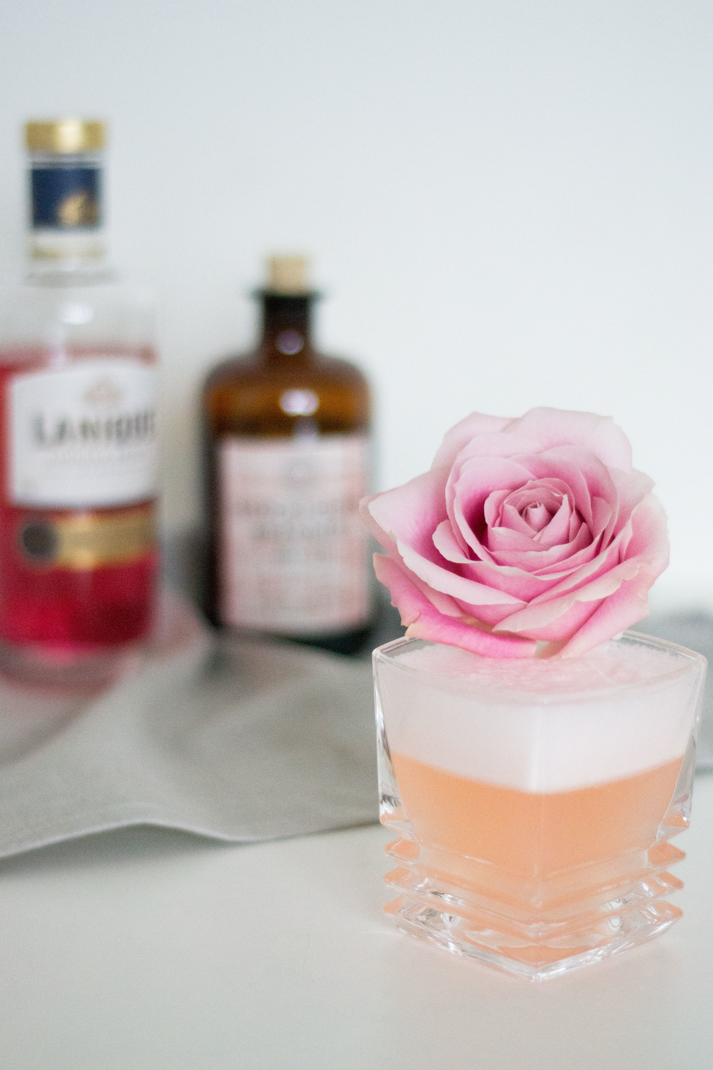 BLOOMING ROSE - - 30ml Gin (I used the lavender/sage/pink grapefruit gin from Stockholms Bränneri)- 30ml Rose liqueur (@laniquedrinks)- 30ml Lemon juice- 15ml Simple syrup (I used ~10)- Egg whiteReverse dry shake all ingredients, double strain into a beautiful rocks glass (a gift from @theelancollective). Garnish with a rose.