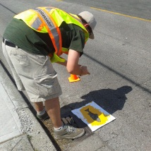 City of Richmond's Sustainability Department research intern, Andrew Weatherill, lays down fish stencils for the student volunteers to paint.